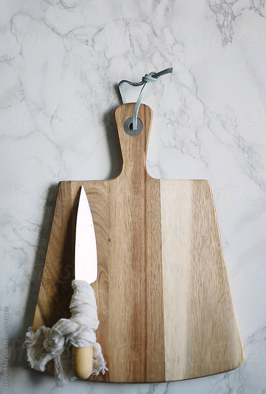 A cutting board and a knife on a marble work surface.  by Darren Muir for Stocksy United