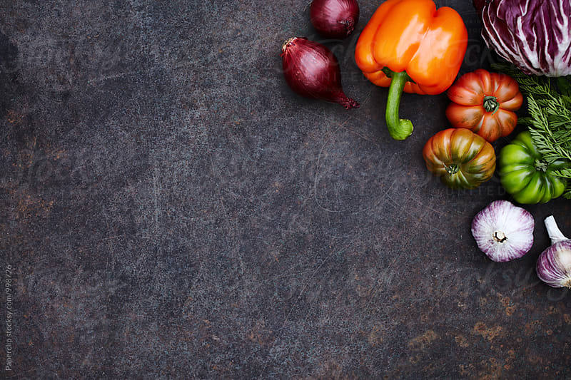 Fresh seasonal vegetables on dark rusty table by Paperclip Images for Stocksy United