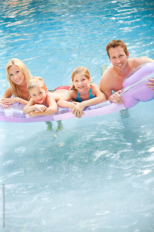 Swimming: Cheerful Family With Inflatible Raft by Sean Locke for Stocksy United