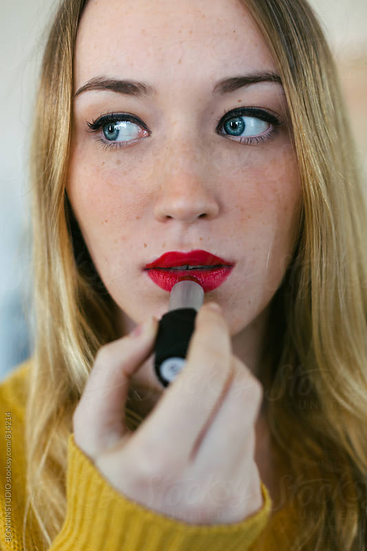 Beautiful woman applying red lipstick. by BONNINSTUDIO for Stocksy United