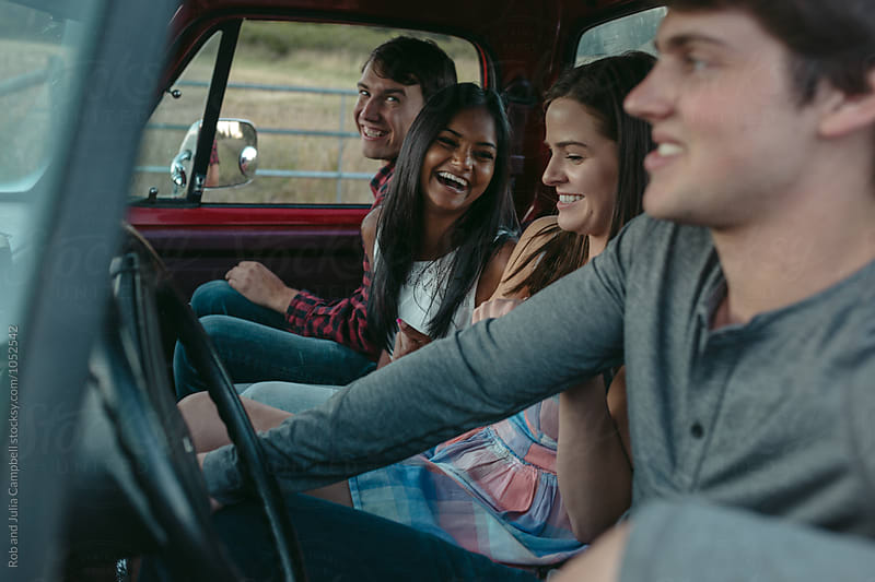 Young friends enjoying summer road trip together in old truck by Rob and Julia Campbell for Stocksy United