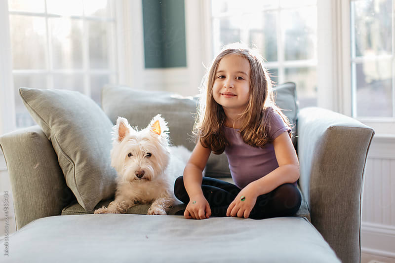 Cute young girl sitting next to a cute little dog on a big chair by Jakob for Stocksy United