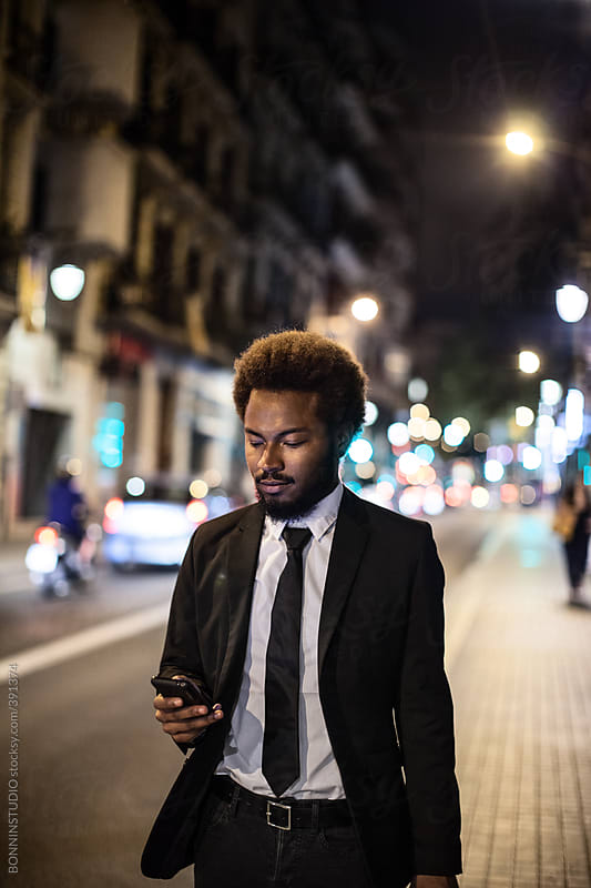 Afro businessman with mobile phone walking on the street at night. by BONNINSTUDIO for Stocksy United