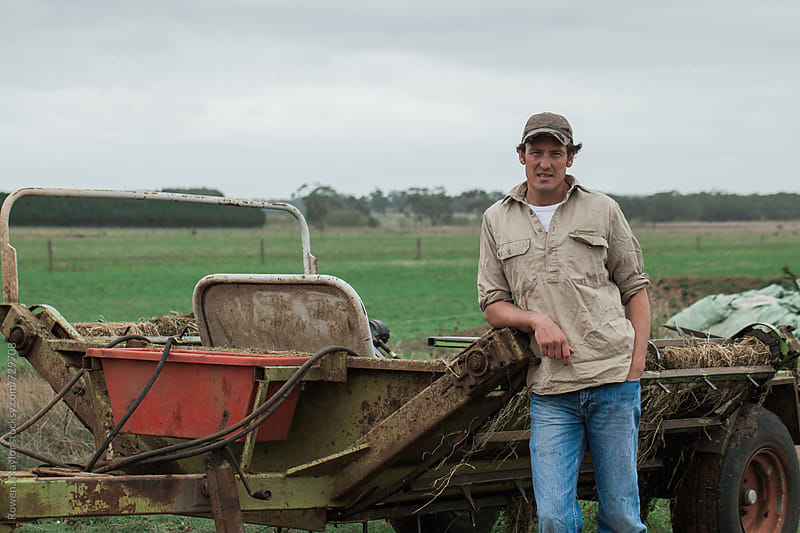 Young Dairy Farmer leaning against farm equipment by Rowena Naylor for Stocksy United