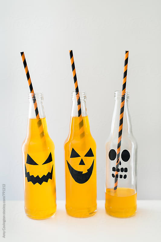 Jack-o'-lantern designs on orange beverages by Amy Covington for Stocksy United