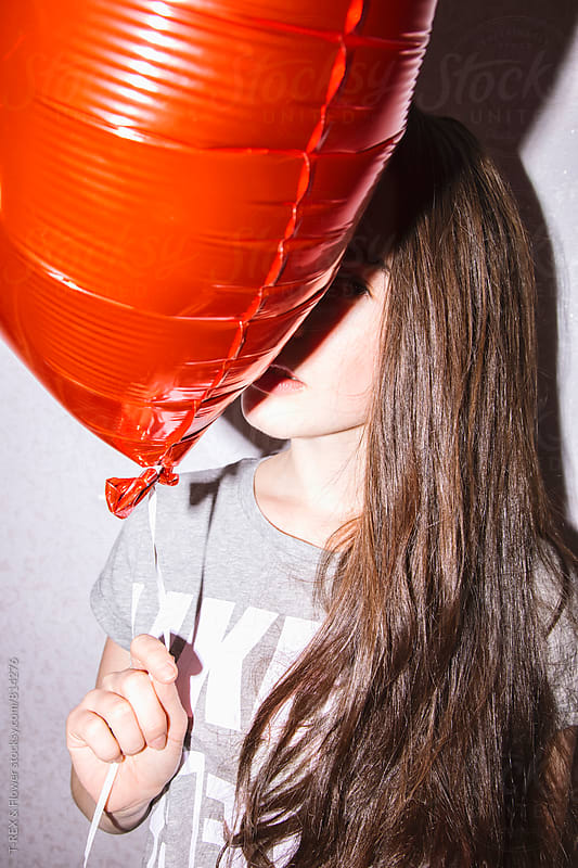 Young woman looking at camera from behind the red balloon by Danil Nevsky for Stocksy United
