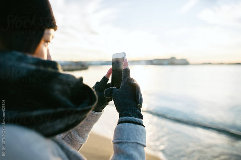 Closeup of woman taking a photo with her phone on the beach on winter. by BONNINSTUDIO for Stocksy United