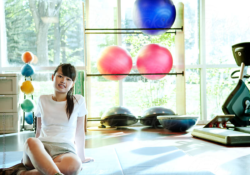 Young Asian woman sitting on a mat at the gym. by W2 Photography for Stocksy United