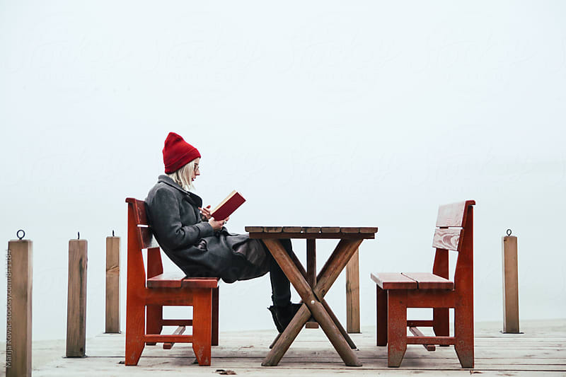 Woman reading a book outdoor during a fog - horizontal by Marija Kovac for Stocksy United