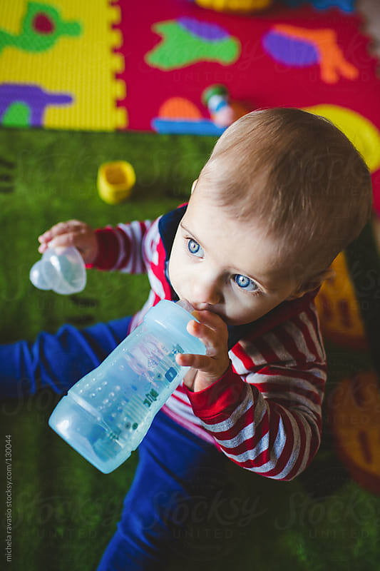 A cute baby drinking water from a bottle by michela ravasio for Stocksy United