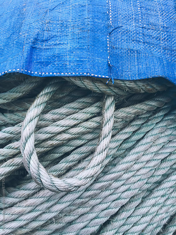 Close up of blue tart covering industrial ropes by Paul Edmondson for Stocksy United