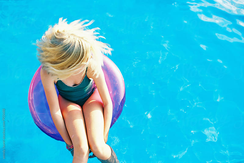 blonde girl with short bob shaking head in pink floatie in blue pool by wendy laurel for Stocksy United