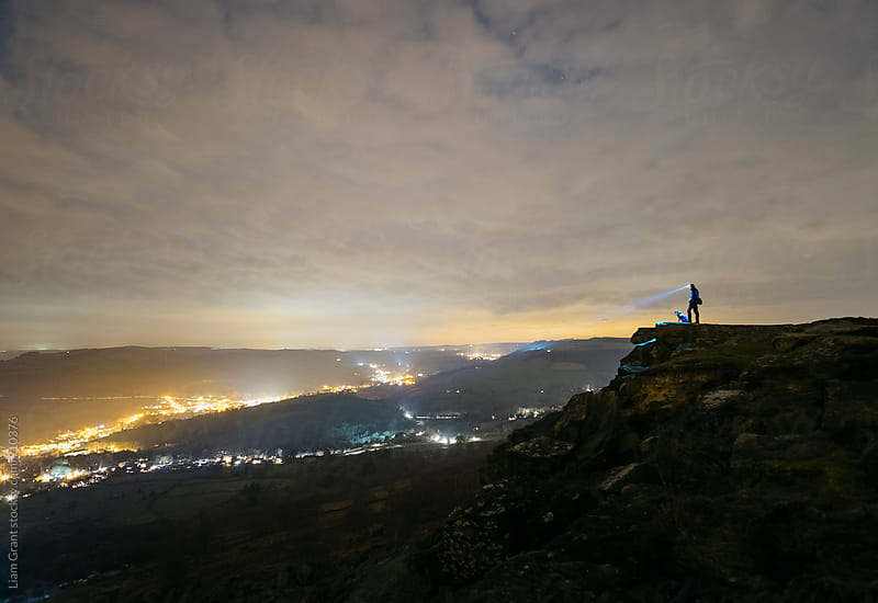 Male and his dog, standing on Curbar Edge at night. Derbyshire, UK. by Liam Grant for Stocksy United