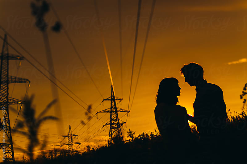 Silhouettes of couple under power lines by Evgenij Yulkin for Stocksy United