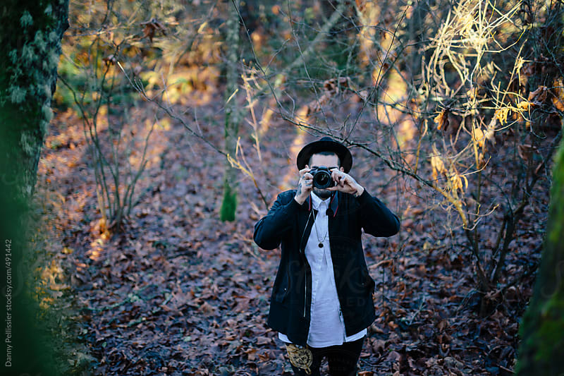 Man in woods taking picture by Danny Pellissier for Stocksy United