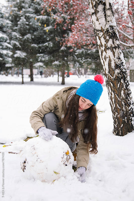 Young brunette woman rolling a snowball by Danil Nevsky for Stocksy United