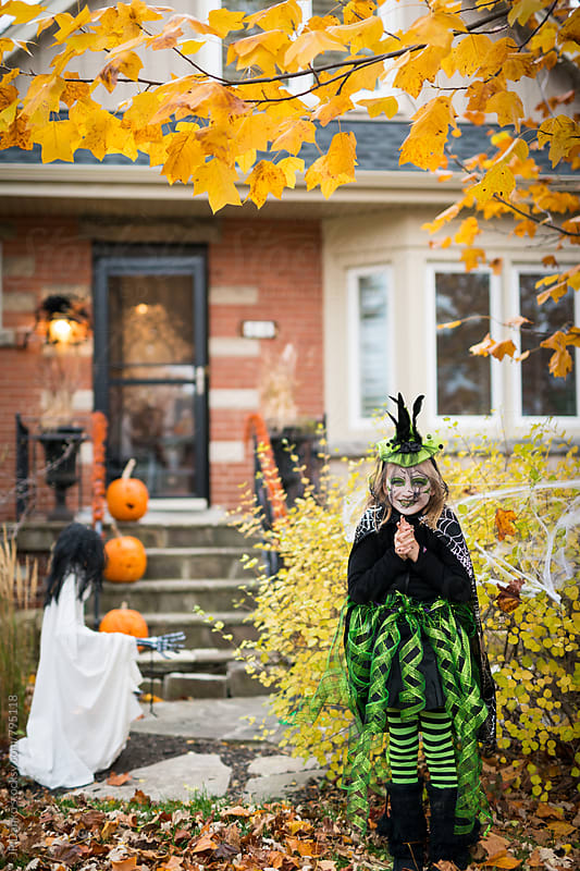 Girl Wearing Witch Costume Excited to Trick or Treat on Halloween by JP Danko for Stocksy United