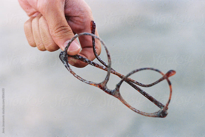 hand holding old glasses found in the sea by Jovo Jovanovic for Stocksy United