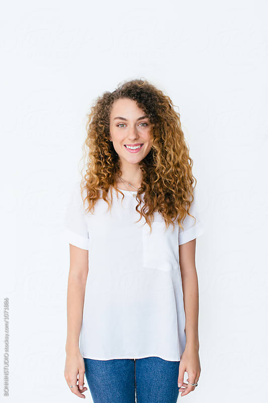 Portrait of a young curly woman standing over white. by BONNINSTUDIO for Stocksy United