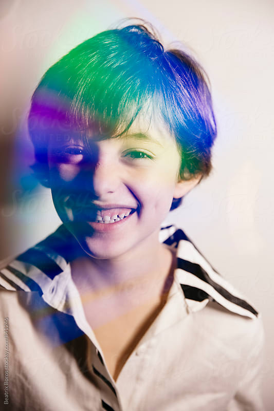 Double exposure of colorful reflection on boy's portrait by Beatrix Boros for Stocksy United