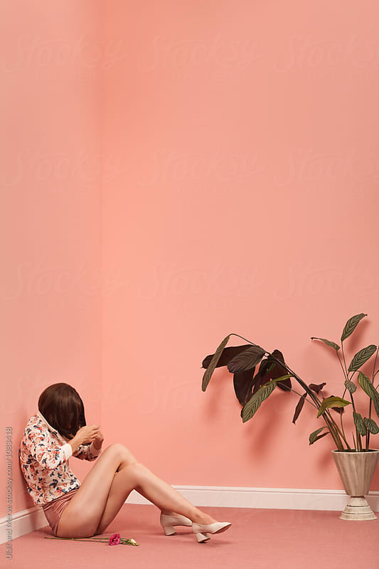 woman sitting on the floor in pink room by Ulaş and Merve for Stocksy United