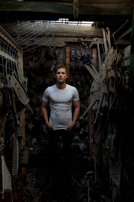 Young man standing amongst car parts by Ben Ryan for Stocksy United