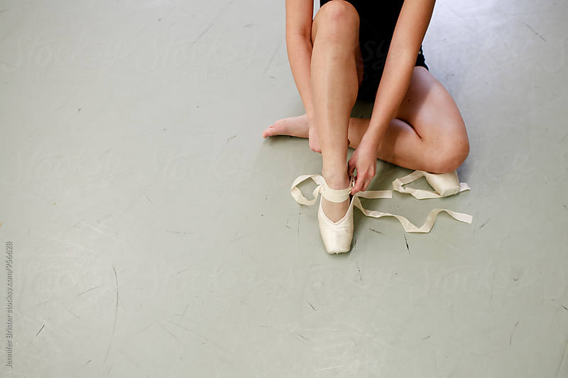 Woman putting on ballet shoes by Jennifer Brister for Stocksy United