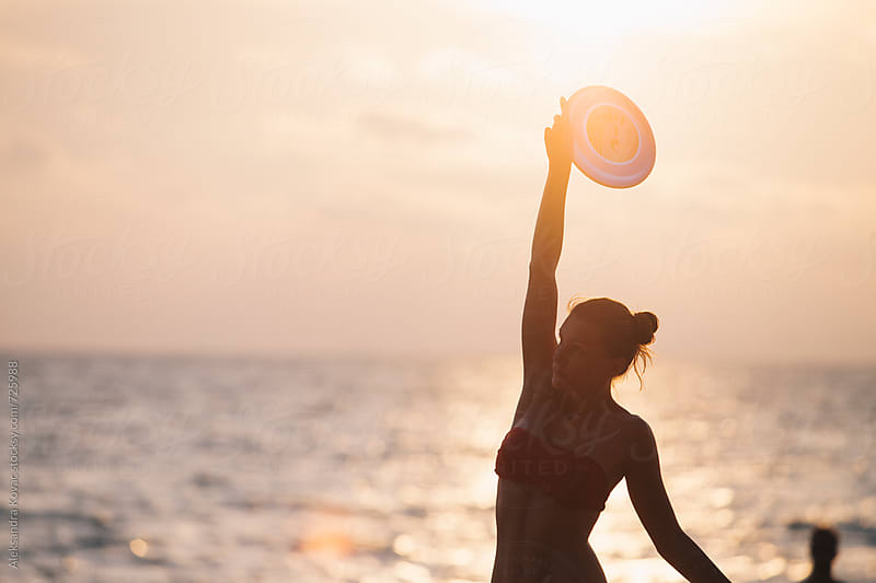 Woman on the beach playing frisbee by Aleksandra Kovac for Stocksy United