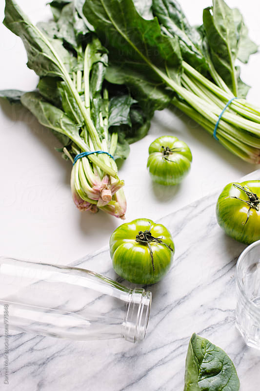 Green tomatoes and spinach bundles on a white background. by Darren Muir for Stocksy United