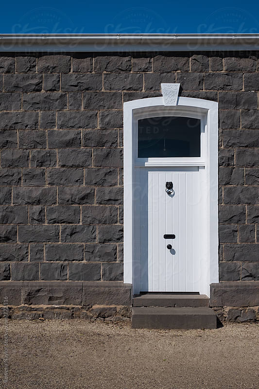 White painted door against heritage bluestone brick by Rowena Naylor for Stocksy United