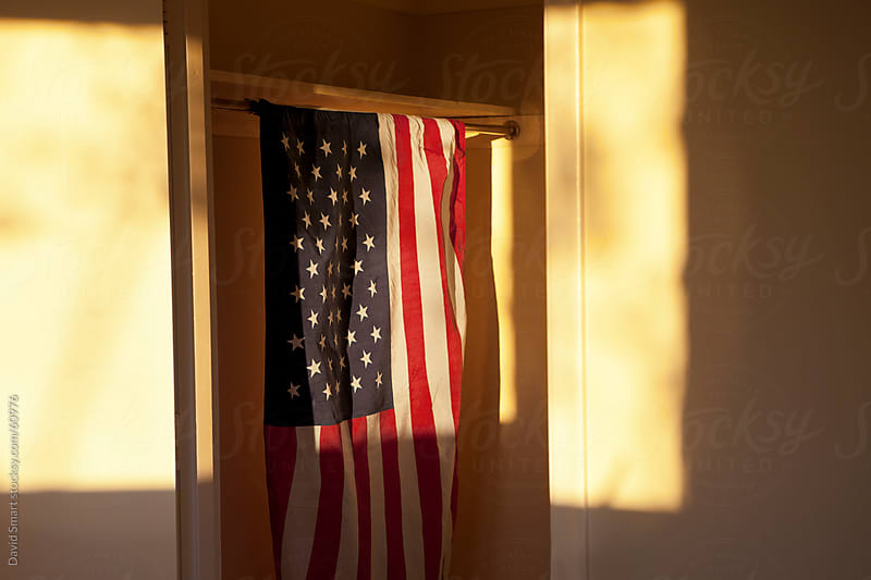 American Flag hanging in a closet with setting sun lighting scene by David Smart for Stocksy United