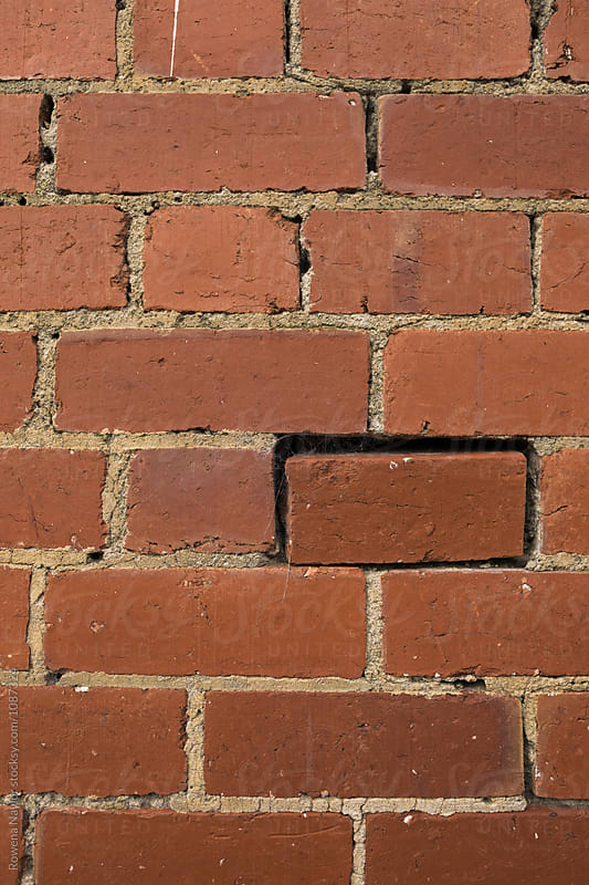 One loose brick in a wall by Rowena Naylor for Stocksy United