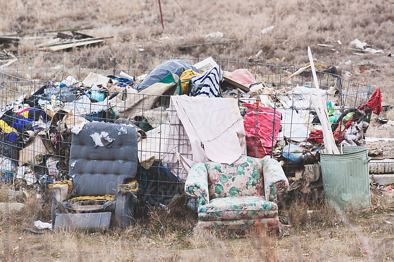A pair of old chairs sit in front of a pile of garbage by Tana Teel for Stocksy United