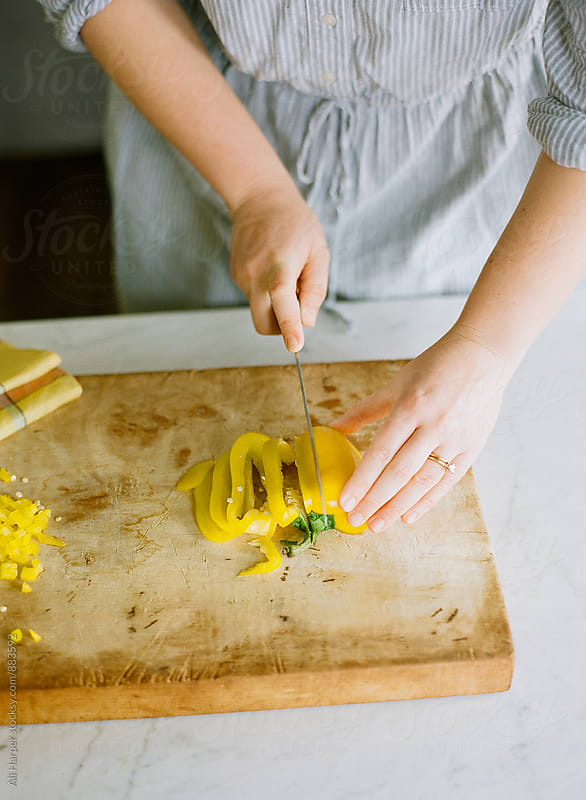 Woman cutting a yellow pepper by Ali Harper for Stocksy United