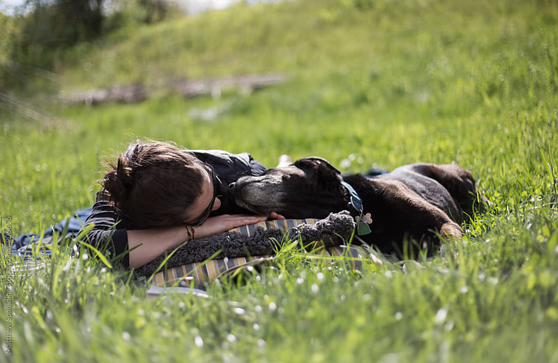 Woman with her pet dog companion relaxing in grass by Matthew Spaulding for Stocksy United