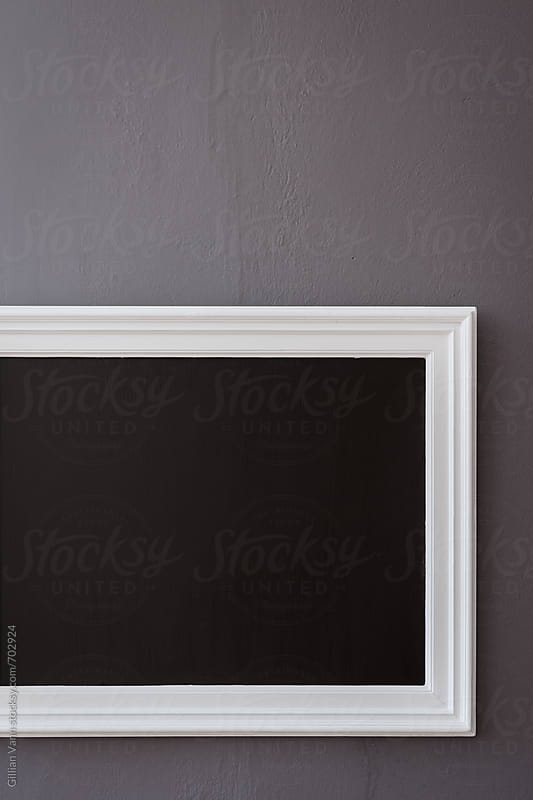 blank blackboard on a wall by Gillian Vann for Stocksy United