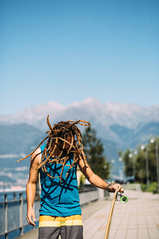 Young man with dreadlocks shaking his head by michela ravasio for Stocksy United