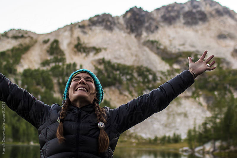 A young woman throws her hands up and smiles in the mountains by Hannah Dewey for Stocksy United