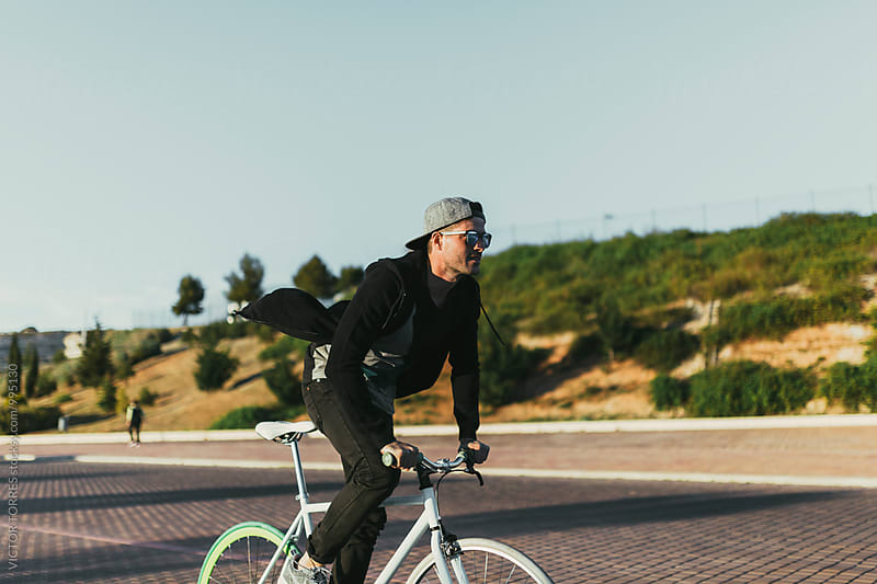Young Man Riding a Bike by VICTOR TORRES for Stocksy United