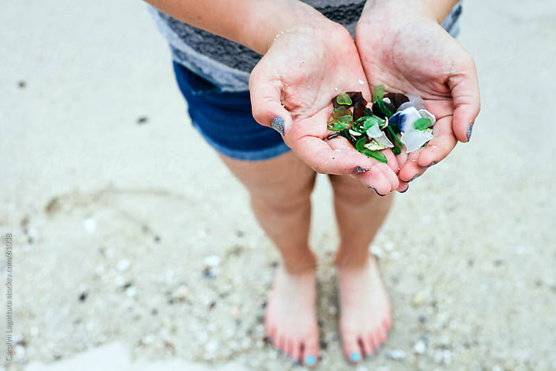 Girl with a handfull of sea glass by Carolyn Lagattuta for Stocksy United