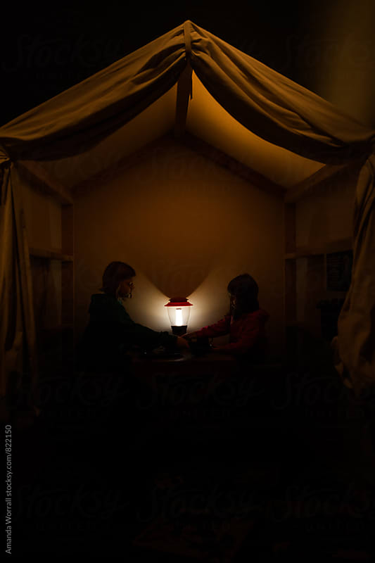 Two children dimly lit by a lantern in an old canvas tent by Amanda Worrall for Stocksy United