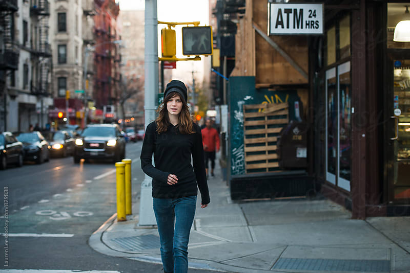 Young woman walking on street in the city by Lauren Naefe for Stocksy United