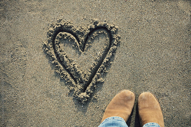 Boots and jeans standing above a heart drawn in the sand by Carolyn Lagattuta for Stocksy United