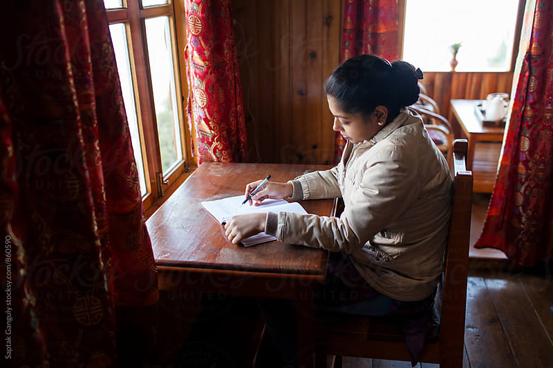 Young woman writing at desk by Saptak Ganguly for Stocksy United