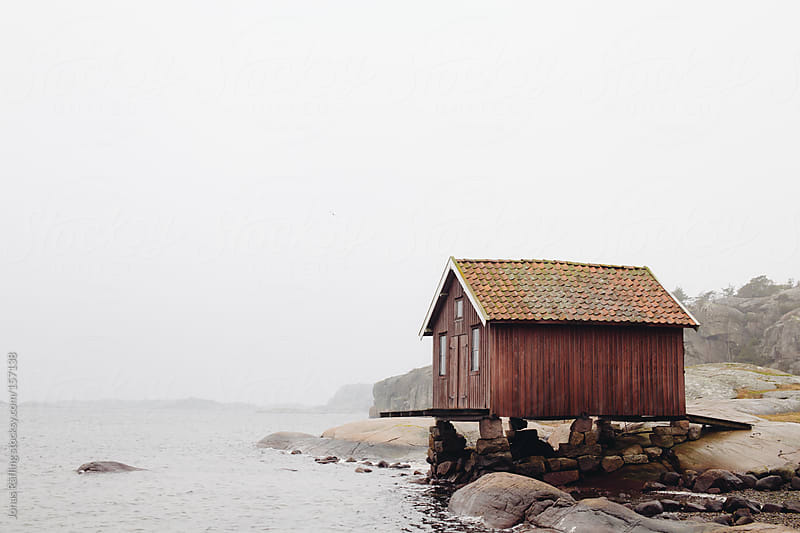 Red fisherman hut in fog by Jonas Räfling for Stocksy United