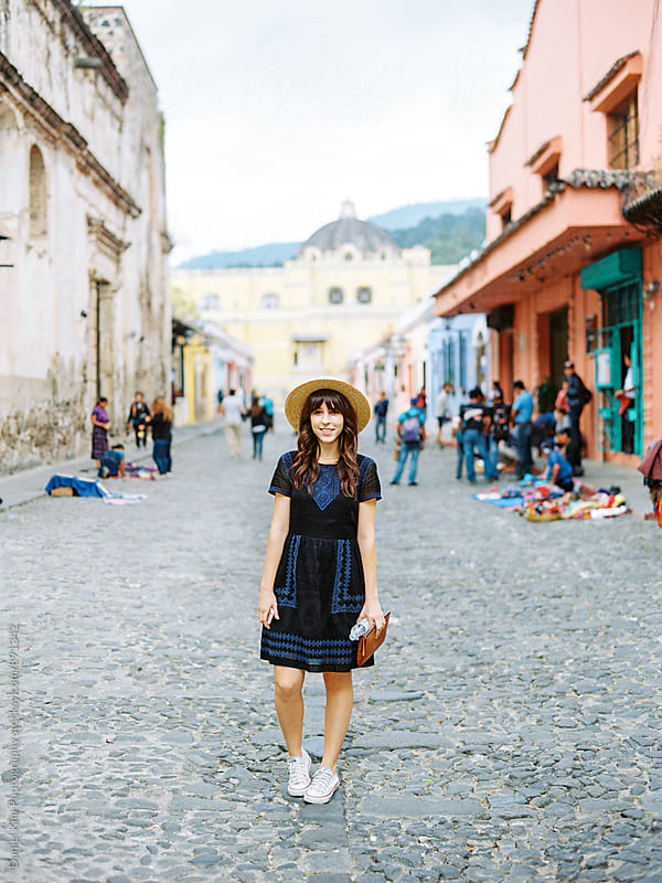 Portrait of woman walking on cobblestone street by Daniel Kim Photography for Stocksy United