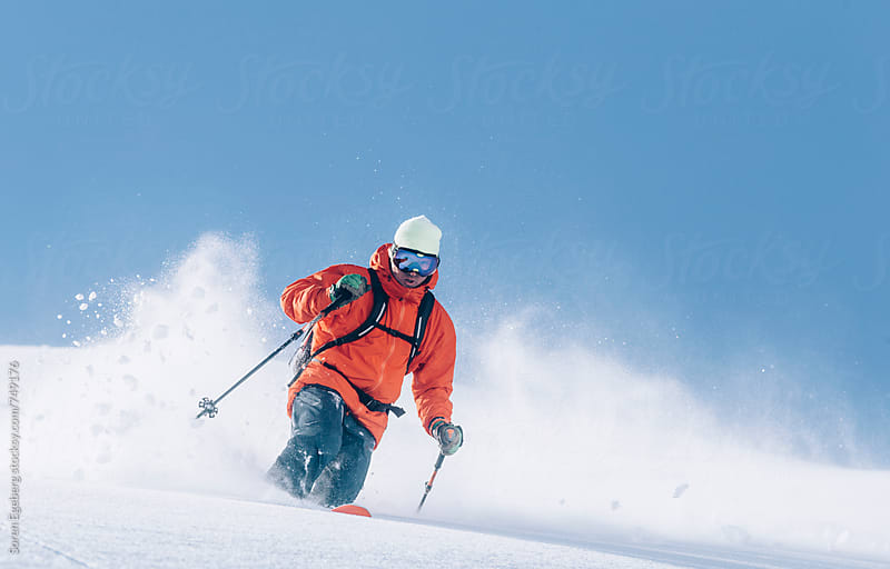 Man skiing deep powder snow in the mountains wearing red jacket by Soren Egeberg for Stocksy United