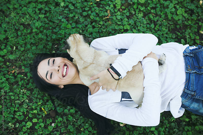 Young woman playing with her pug-dog by Jovana Rikalo for Stocksy United