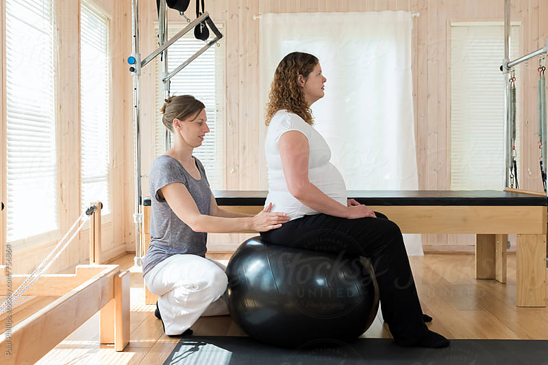 Pregnant woman being guided through an exercise routine whilst seat on a pilates ball by Paul Phillips for Stocksy United