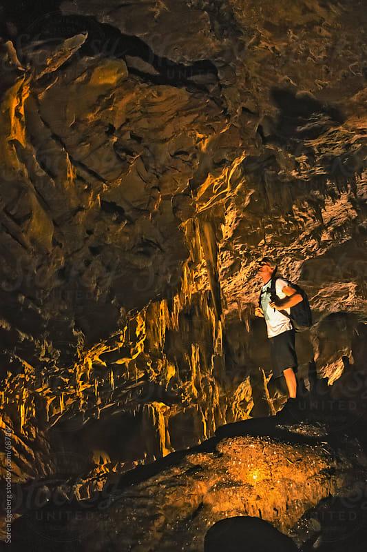 Man standing inside limestone cave by Soren Egeberg for Stocksy United